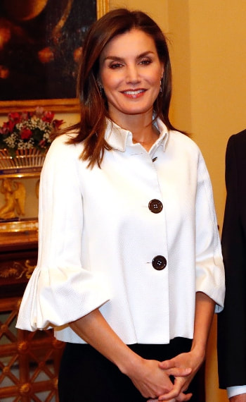 Queen Letizia wears textured white peplum jacket with cropped bell sleeves and oversized black buttons.